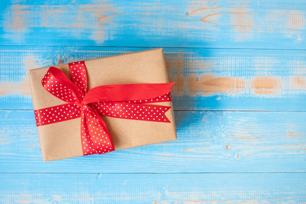 Geschenkbox der frohen weihnachten oder valentine present auf blauem hölzernem hintergrund Premium Fotos