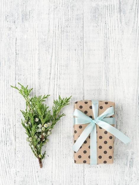 Geschenkbox eingewickelt in braunes papier und zweig auf weißem holztisch, kopienraum. Premium Fotos
