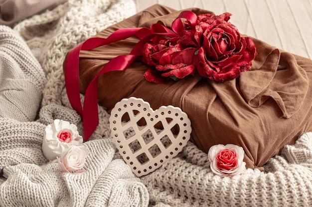 Geschenkbox mit bändern und dekorativen rosen auf strickwaren. ursprüngliche geschenkverpackung für valentinstag. Kostenlose Fotos