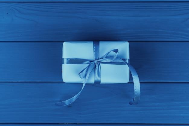 Geschenkbox mit band auf blauem hintergrund, draufsicht Premium Fotos