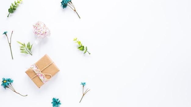 Geschenkbox mit blumenniederlassungen auf weißer tabelle Kostenlose Fotos