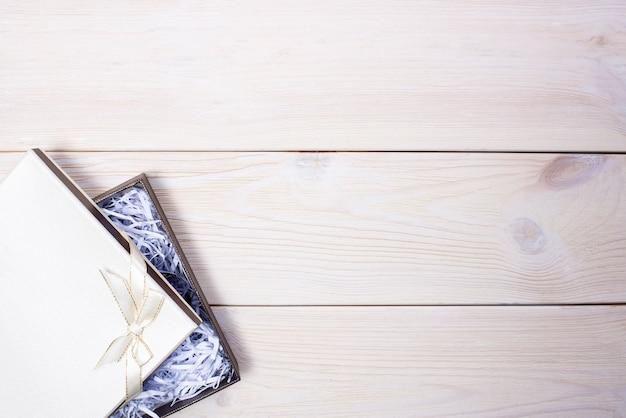 Geschenkbox mit bogen auf hölzernem hintergrund Premium Fotos