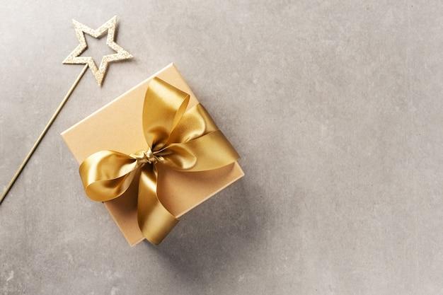 Geschenkbox mit goldenem band auf grau Premium Fotos