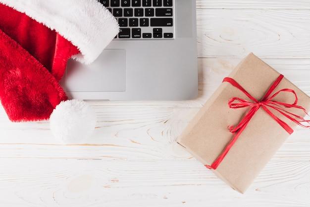 Geschenkbox mit laptop auf holztisch Kostenlose Fotos