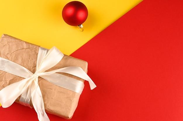 Geschenkbox mit lichtbogen und weihnachtskugel auf gelb-rotem hintergrund. Premium Fotos