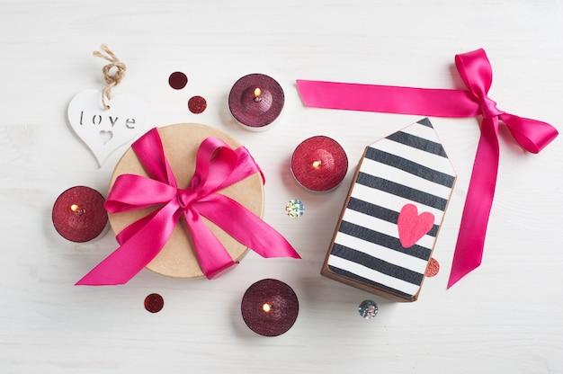 Geschenkbox mit rosa schleife und brennenden kerzen Premium Fotos