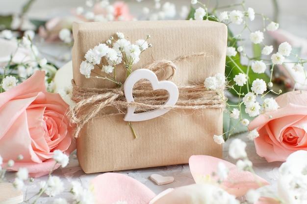 Geschenkbox mit rosen und kleinen weißen blumen auf grauem hintergrund Premium Fotos