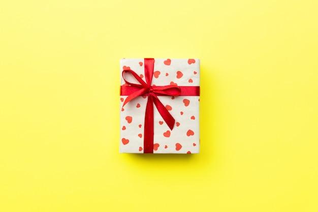 Geschenkbox mit rotem band und herz auf gelbem hintergrund, draufsicht mit kopienraum für text Premium Fotos