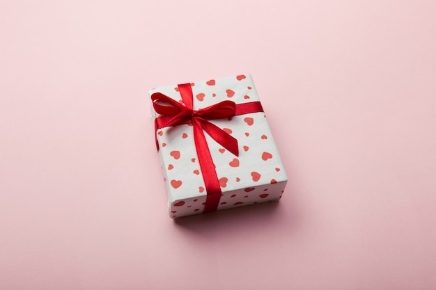 Geschenkbox mit rotem band und herz auf koralle Premium Fotos
