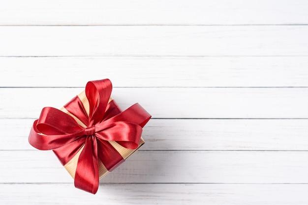 Geschenkbox mit rotem bogen auf einem weißen hölzernen hintergrund mit kopienraum Premium Fotos