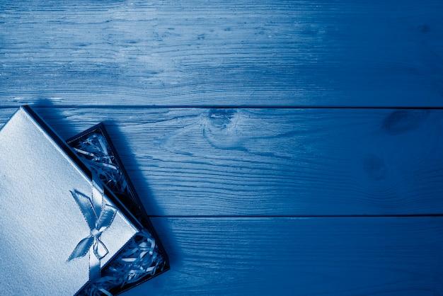 Geschenkbox mit schleife auf einem holztisch, in einem modischen klassischen blau getönt Premium Fotos