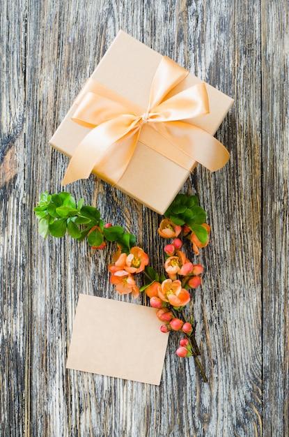 Geschenkbox mit schleifenband, leerem etikett und zartem blühendem zweig. Premium Fotos