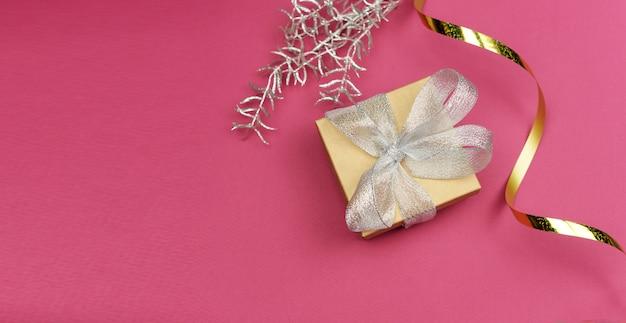 Geschenkbox mit silberner schleife und goldenem serpentin Premium Fotos