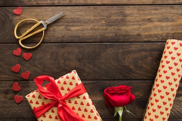 Geschenkbox nahe rolle des sweetiepapiers, -scheren und -blüte Kostenlose Fotos