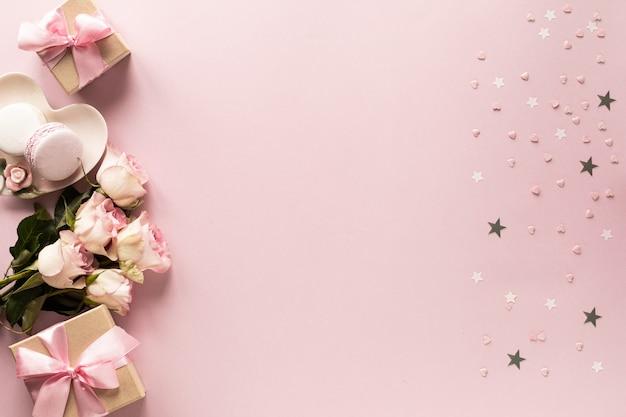 Geschenkbox oder geschenkbox und blumen auf rosa tischoberansicht. Premium Fotos