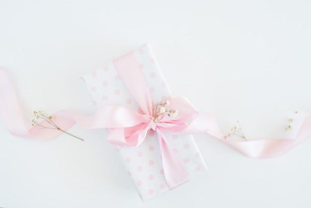 Geschenkbox tupfenpapier, rosa schleife, kleine blumen. frauentag Premium Fotos