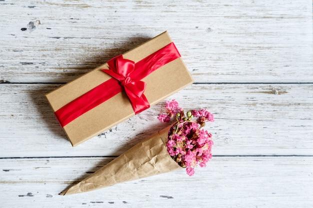 Geschenkbox und blumen auf holz Premium Fotos