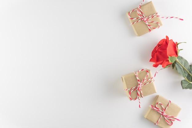 Geschenkbox und rotrosenblume lokalisiert auf weißem hölzernem beschaffenheitshintergrund Premium Fotos