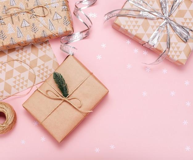 Geschenkboxen im kraftpapier auf rosa hintergrund. flach liegen. kopieren sie platz. Premium Fotos