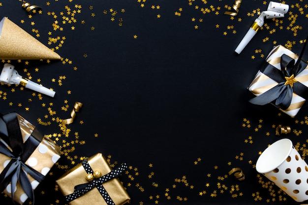 Geschenkboxen in den verschiedenen goldmusterpackpapieren über sternförmigen goldenen pailletten auf einem schwarzen hintergrund. Premium Fotos