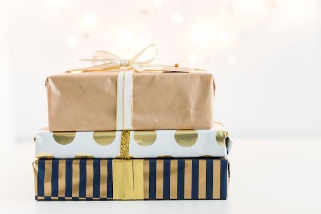 Geschenkboxen in sweetie-papieren in der nähe von lichterketten Kostenlose Fotos