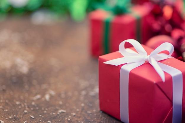 Geschenkboxen mit einem weißen bogen gegen ein hintergrund-bokeh des funkelns Premium Fotos