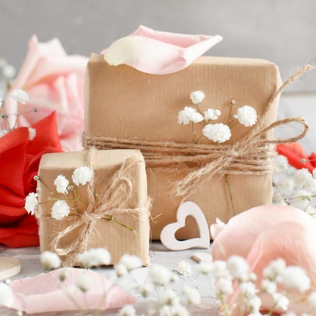 Geschenkboxen mit kleinen weißen blumen und herzen auf grauem hintergrund Premium Fotos