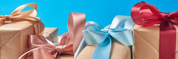 Geschenkboxen mit rotem bogen auf einem blauen hintergrund, fahne Premium Fotos