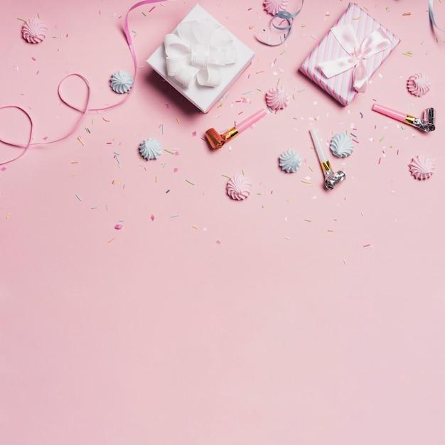 Geschenkboxen mit süßigkeiten und parteigebläse auf rosa hintergrund Kostenlose Fotos