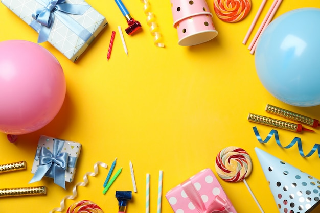 Geschenkboxen und geburtstagszubehör auf gelbem hintergrund, platz für text Premium Fotos