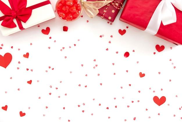 Geschenkboxen und süßigkeiten auf roter herzpapierbeschaffenheit Premium Fotos