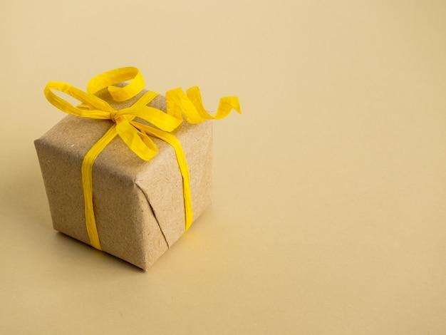 Geschenke im gelben stil auf gelber oberfläche. geschenke in kraftpapier verpackt Premium Fotos