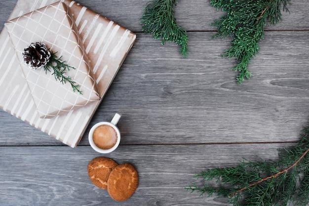 Geschenke in der nähe von zweigen, tasse getränk und kekse Kostenlose Fotos