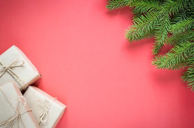 Geschenke in umweltfreundlichen bastelverpackungen für den urlaub und tannenfichte auf rotem grund mit kopierraum. Premium Fotos