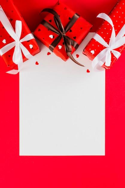 Geschenke und herzen über leerem papier Kostenlose Fotos