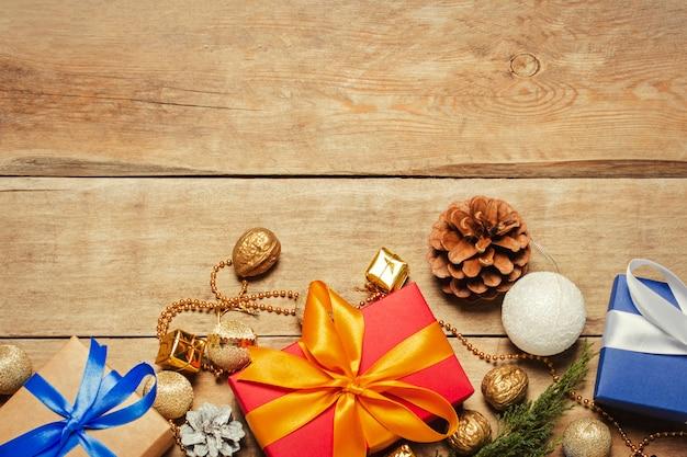 Geschenke und weihnachtsdekorationen, weihnachtsbaumast auf einem hölzernen hintergrund. weihnachten, winterferien,. flachgelegt, draufsicht Premium Fotos