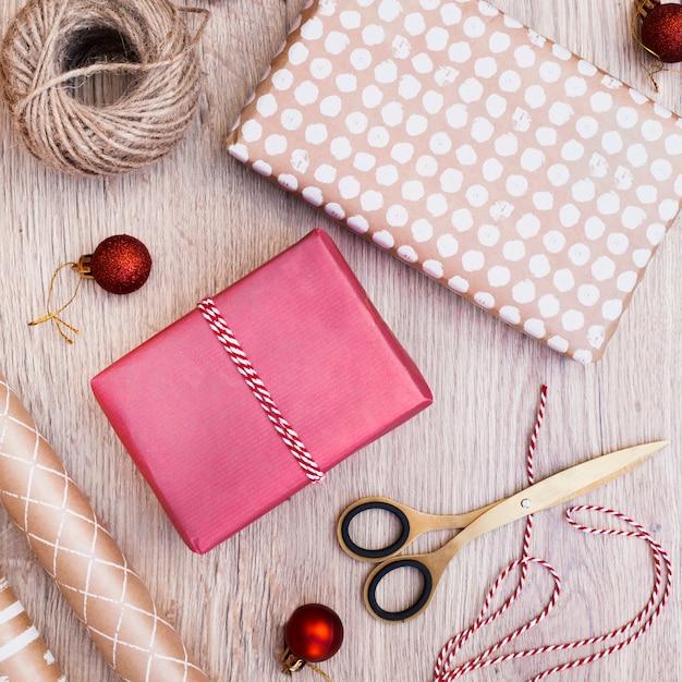 Geschenke verpackt in der nähe von weihnachtskugeln, fäden und scheren Kostenlose Fotos