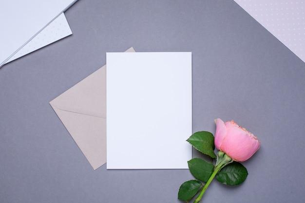 Geschenkkarte und umschlag mit rosarose auf grau Premium Fotos