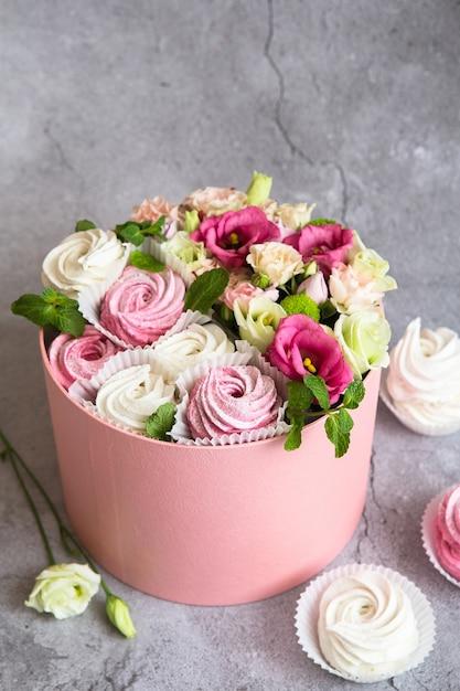 Geschenkset in der box - weiße und rosa marshmallows und schöne blumen Premium Fotos