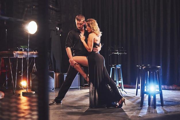 Geschickte tänzer, die in einem dunklen raum unter licht auftreten. Kostenlose Fotos