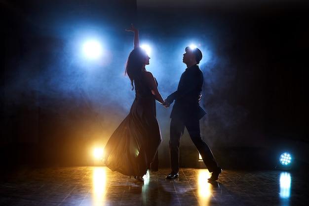 Geschickte tänzer treten im dunklen raum unter dem licht und dem rauch des konzerts auf. sinnliches paar, das einen künstlerischen und emotionalen zeitgenössischen tanz aufführt Kostenlose Fotos