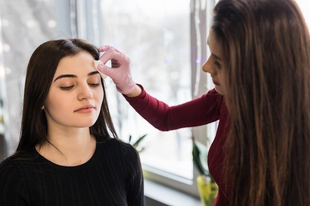 Geschickte visagistin, die augenbrauen für eine junge frau mit dunklem haar schminken lässt Kostenlose Fotos