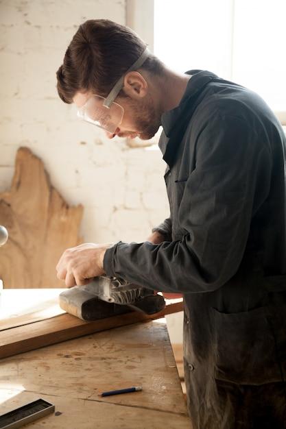 Geschickter junger tischler, der holzarbeiten herstellt, mit elektrischem schleifer arbeitet, vertikal Kostenlose Fotos