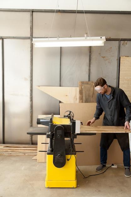 Geschickter tischler, der an der werkzeugmaschine arbeitet Kostenlose Fotos