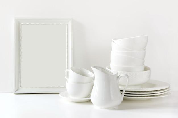 Geschirr, teller, geräte und anderes unterschiedliches weißes material auf weiße tischplatte. Premium Fotos