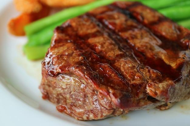 Geschlossen herauf gegrilltes lendenstück-steak mit unscharfem gemüse im hintergrund Premium Fotos