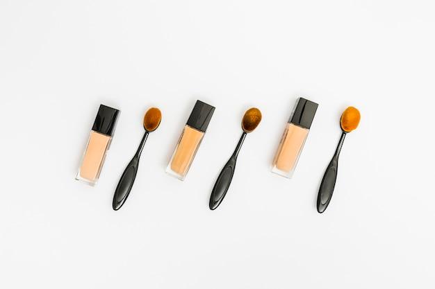 Geschlossene flaschen flüssiger grundierung mit ovaler make-upbürste auf weißem hintergrund Kostenlose Fotos