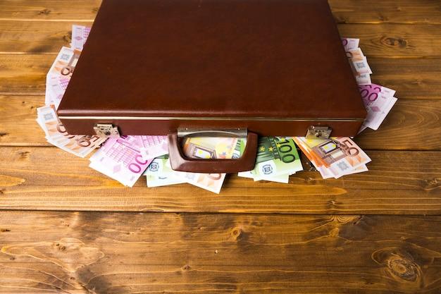 Geschlossener koffer des hohen winkels mit geld Kostenlose Fotos