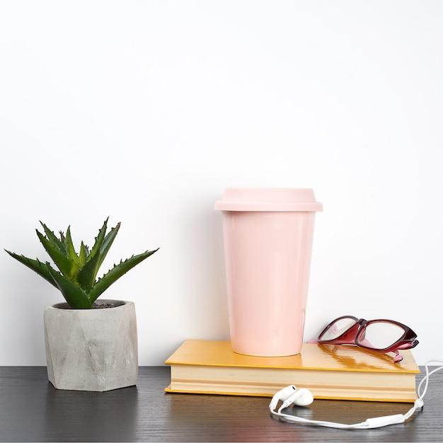 Geschlossenes buch und rosa keramikglas mit kaffee auf einer schwarzen tabelle Premium Fotos