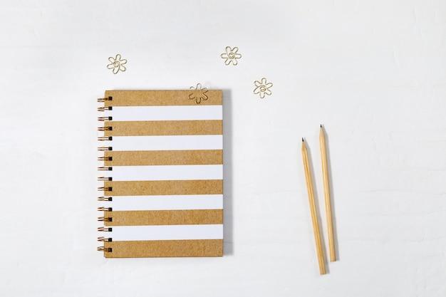 Geschlossenes notizbuch auf frühling mit gold zeichnete abdeckung und hölzernen bleistift auf weißer tabelle. schulheft mit metallklammern. ansicht von oben. Premium Fotos